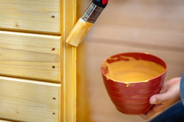 Woman glazes or paints wooden boards with pines colored glaze or varnish
